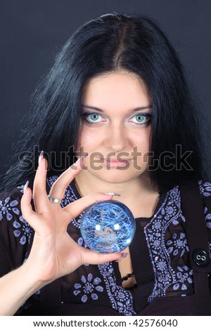 Beautifu smiling black-haired witch holding the magic sphere - stock photo
