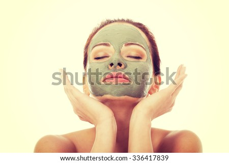 Beautifu toplessl woman with facial mask having her eyes closed. - stock photo