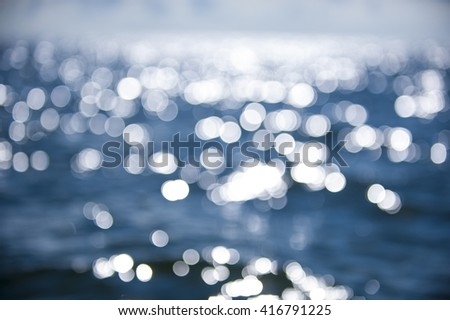 Beautiful abstract background bokeh sun light reflections on blue aqua water sailing boat - stock photo