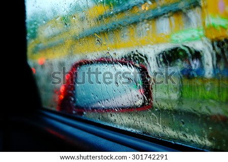 Beautiful abstract image of rain drops on a red car side view mirror and window, with street on a background, close up - stock photo