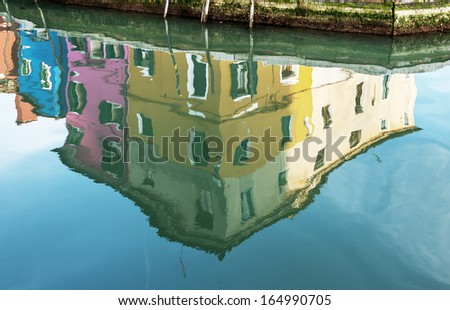 Beautiful abstract reflections in the water channel of colored houses - Burano, Venice, Italy