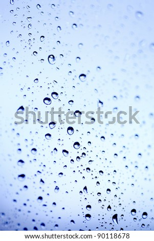 Beautiful abstraction with water drops over blue glass background(shallow dof)