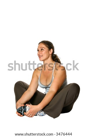 Beautiful active woman in sports attired sitting down on the floor, doing her stretching exercise, isolated on white. - stock photo