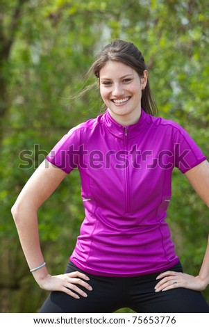 Beautiful active young woman outdoors doing stretch exercises - stock photo