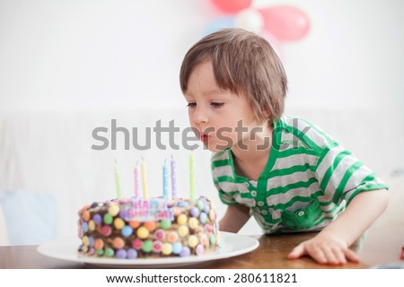 Beautiful adorable four year old boy in green shirt, celebrating his birthday, blowing candles on homemade baked cake, indoor. Birthday party for kids - stock photo