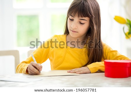 beautiful adorable girl writing  greeting card