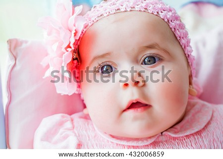 Beautiful adorable little girl in a pink dress with a bow. Happy childhood of the child. Closeup, macro. - stock photo