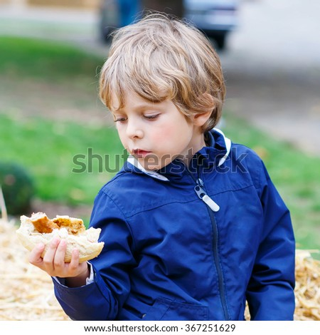Beautiful adorable little kid boy eating hot dog or German sausage on thanksgiving or halloween pumpkin festival, outdoors. child enjoying warm autumn day. - stock photo
