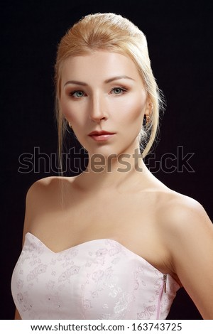 Beautiful adult blond skinny woman posing to camera over dark background - stock photo
