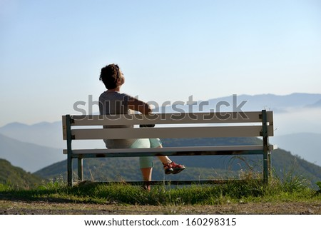 Beautiful adult brunette woman sits on a bench in high mountain above clouds  under bright sunlight  , Greece