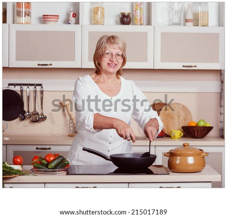 Beautiful adult multiracial woman while making lunch. Adult woman working in the kitchen. Mom while she work something else. Mother prepares. Cooking concept. Woman while preparing food in kitchen.  - stock photo