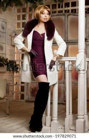 Beautiful adult woman in a winter coat with fur. Trendy modern blondy girl with short hair - stock photo