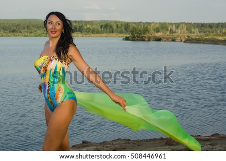 Beautiful adult woman in bikini and with pareo relaxing on the beach by the lake