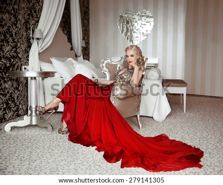 Beautiful adult woman in fashion red dress sitting on modern armchair at luxurious interior apartment with furniture. - stock photo