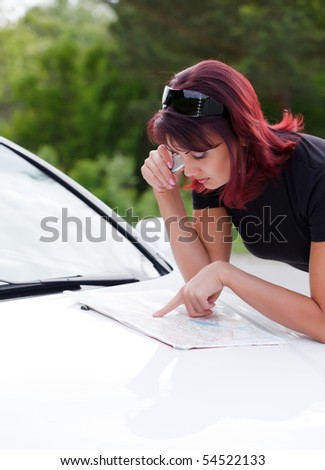 Beautiful Adult Woman Looking At A Map On The Hood Of Her Car.