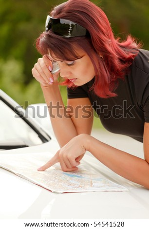 Beautiful Adult Woman Looking At A Map On The Hood Of Her Car