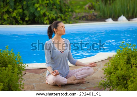 beautiful adult woman practicing yoga in the lotus position near the pool - stock photo