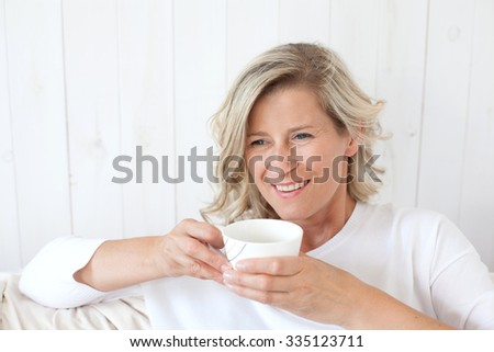 beautiful adult woman with blond hair, smiling, happy drinking coffee, tea.He is sitting on the sofa with a cup in hand. - stock photo