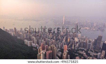 Beautiful aerial shot of many high  skyscrapers covered with sunset fog or haze in Hong Kong, China. Top view of Victoria Harbour from Victoria Peak at sunset. City skyline.