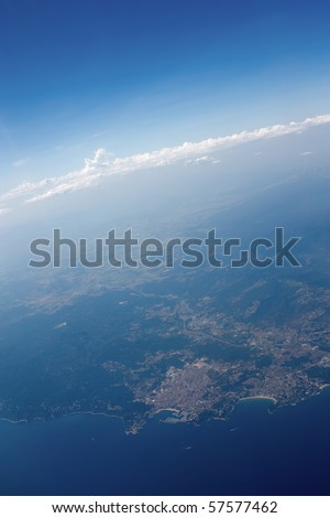Beautiful aerial view from the plane on spanish coastline with clouds and skyline in the back. - stock photo