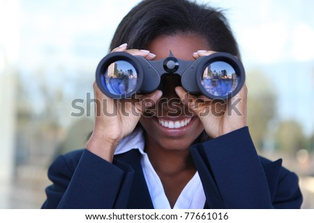 Beautiful african american business woman looking through binoculars - stock photo