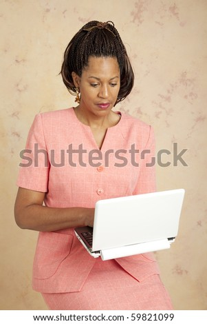 Beautiful african american businesswoman checks email on her wireless netbook computer. - stock photo