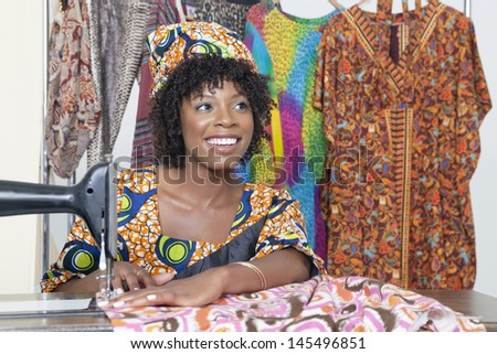 Beautiful African American female tailor looking away while stitching cloth on sewing machine - stock photo