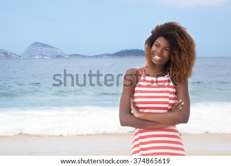 Beautiful african american girl with crazy hairstyle and striped dress at beach - stock photo