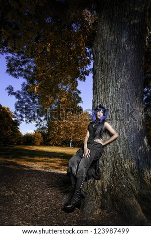 Beautiful african american gothic woman leaning against a large tree. Beautiful, vibrant fall like colors surrounding her. - stock photo
