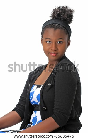 Beautiful African American Haitian teen girl wearing a dress and sweater with her hair up is sitting on a chair.  Photographed on a white background. Space for copy. - stock photo