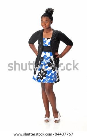 Beautiful African American Haitian teen girl wearing a dress, sweater and heels with her hair up.  Posing and smiling on a white background.  Space for copy. - stock photo