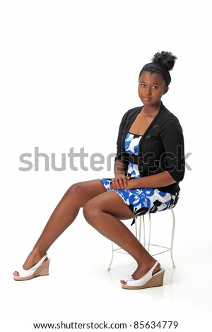 Beautiful African American Haitian teen girl wearing a dress, sweater and heels with her hair up is sitting on a chair.  Photographed on a white background. Space for copy. - stock photo