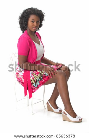Beautiful African American Haitian teen girl wearing a pink and white dress and heels, sitting in a chair.  Photographed on a white background. Space for copy. - stock photo