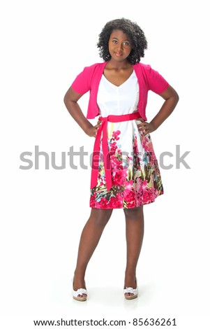 Beautiful African American Haitian teen girl wearing a pink sweater and white and pink print dress, stands with her hands on her hips, smiling.  Photographed on a white background. Space for copy. - stock photo