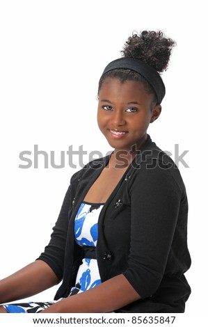 Beautiful, African American Haitian teen girl with her hair up.  She wears braces on her teeth and is smiling with warm eyes and expression. Photographed on a white background. Space for copy.