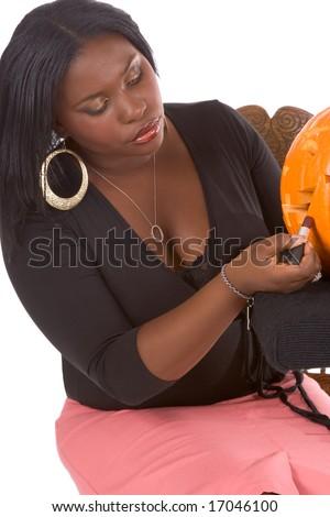 Beautiful African-American make up artist applying makeup on Halloween carved pumpkin (Jack O' Lantern) (focus on pumpkin) - stock photo