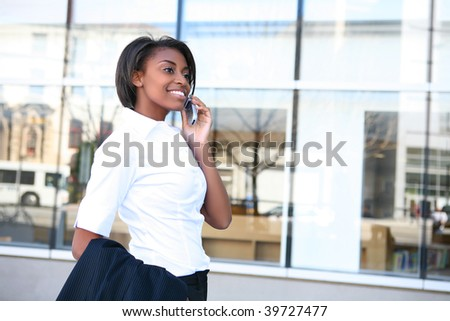 Beautiful african american student woman on the cell phone in front of library - stock photo