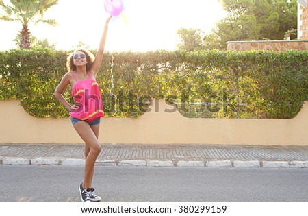 Beautiful african american teenager girl with joyful expression, fun in a home exterior suburban street, holding balloons up in the air, laughing outdoors sunset. Fashionable adolescent lifestyle.