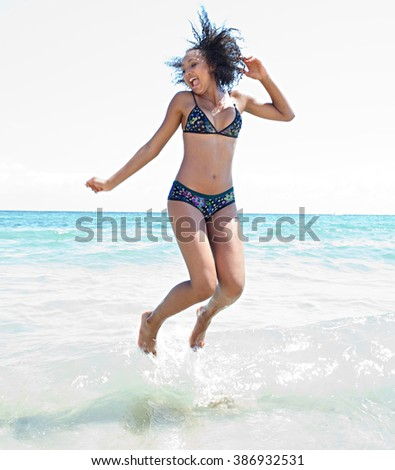 Beautiful african american teenager young woman jumping in the blue sea, joyful sunny summer holiday, coastal exterior. Adolescent travel lifestyle enjoying the sun and clear sea beach, body figure. - stock photo