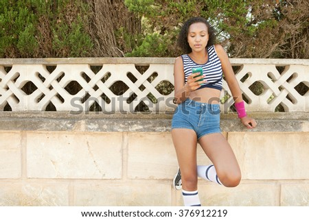 Beautiful african american teenager young woman networking using a smart phone on a summer holiday, in suburban exterior. Adolescent technology lifestyle, fashionable sporty living.  - stock photo