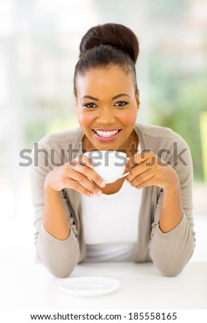 beautiful african american woman drinking coffee at home - stock photo