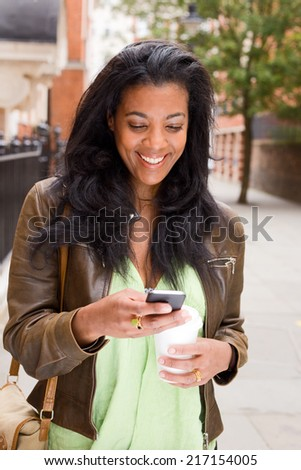 beautiful african american woman enjoying coffee and checking her mesages.  - stock photo
