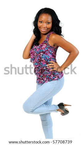 Beautiful african american woman in bright top kicking one leg up - smiling - stock photo