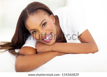 beautiful african american woman lying on bed - stock photo