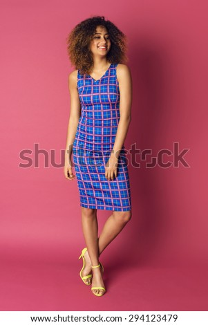 Beautiful African American woman posing in nice checked dress on a pink background. Fashion photo with afro hairstyle.