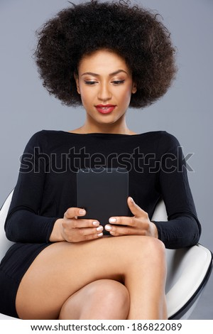 Beautiful African American woman reading her tablet as she sits in a modern armchair in an elegant black dress, close up view - stock photo
