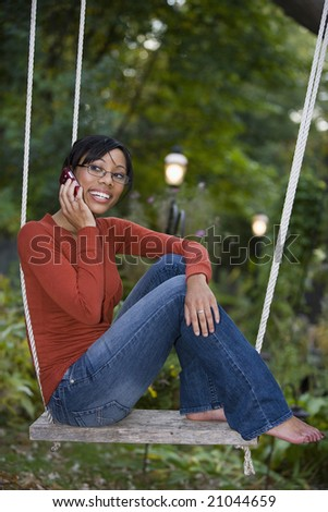 Beautiful African American woman sitting outside on a swing talking on her cell phone - stock photo