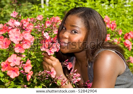 Beautiful African American woman smelling flowers - stock photo