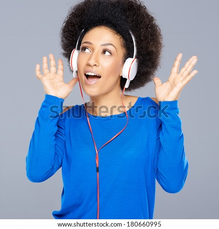 Beautiful African American woman with a fun afro hairstyle enjoying her music listening to her earphones and singing along to the tune - stock photo
