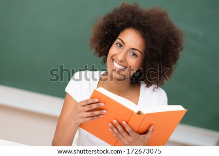 Beautiful African American woman with an afro hairstyle sitting in class at university holding a large textbook, green blackboard background - stock photo